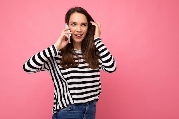 Foto de uma jovem atraente e emocional falando no smartphone usando um suéter listrado