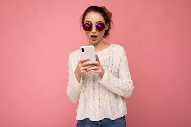 Foto de uma jovem atraente e insatisfeita, chocada, usando blusa branca casual e óculos de sol coloridos