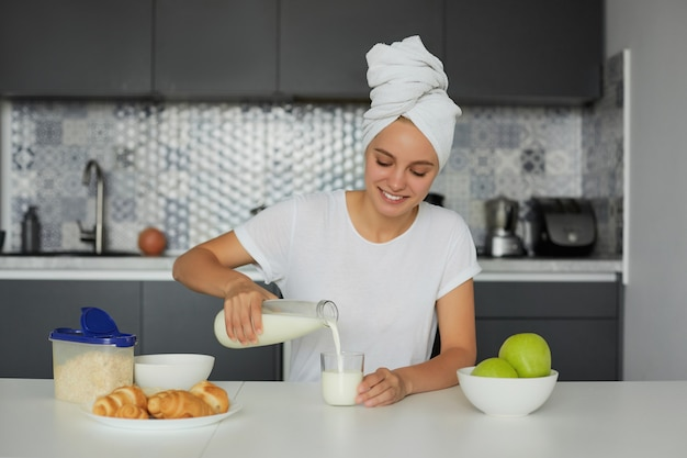 Foto de uma jovem atraente loira sentada à mesa pela manhã, sorrindo, olhando para um copo de leite