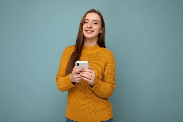 Foto de uma jovem atraente, positiva, de boa aparência, vestindo uma roupa casual elegante, posando