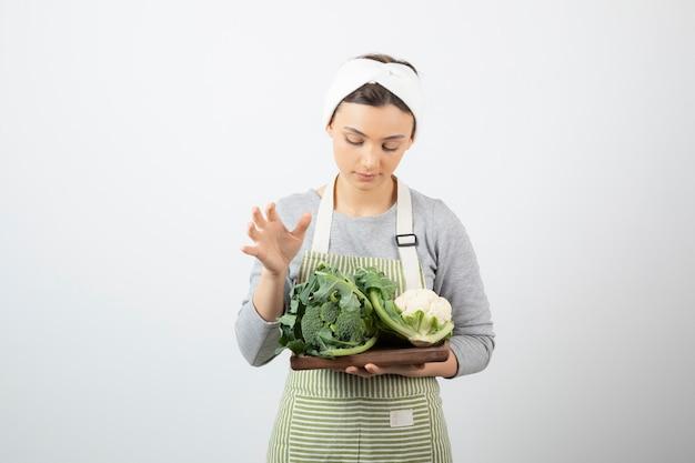 Foto de uma jovem atraente segurando um prato de madeira com couve-flor e brócolis