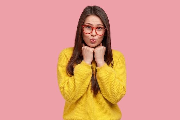Foto de uma jovem bonita com as mãos nos punhos sob o queixo, lábios dobrados, óculos transparentes, suéter amarelo casual