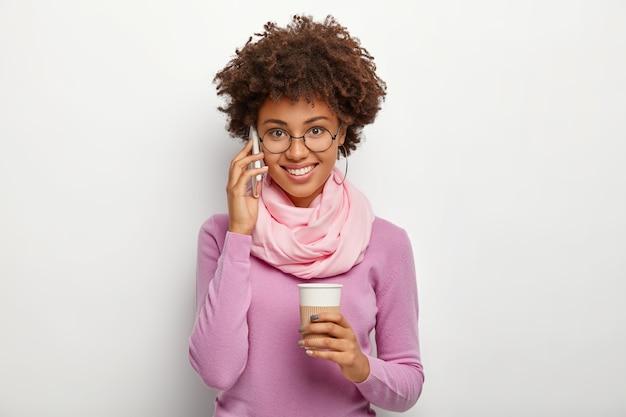 Foto de uma jovem bonita com cabelo escuro e crespo, que gosta de uma conversa agradável ao telefone, segura uma xícara de café para viagem, usa óculos redondos, suéter roxo, é falante, usa tecnologias modernas