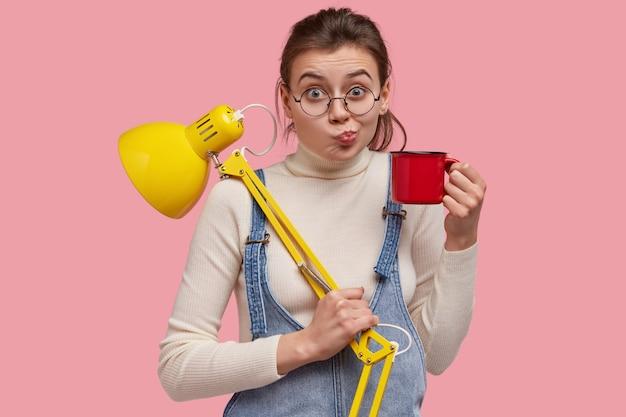 Foto de uma jovem bonita franze os lábios, carrega uma caneca com chá e uma luminária de mesa amarela, pronta para estudar