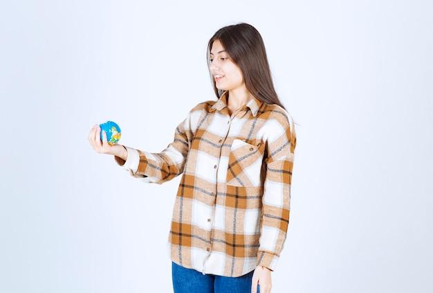 Foto de uma jovem bonita olhando para o globo pequeno na parede branca.