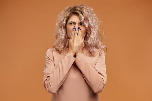 Foto de uma jovem careta, descontente e enojada, com um penteado estiloso beliscando o nariz por causa do cheiro desagradável proveniente de comida estragada na geladeira. fedor, nojo