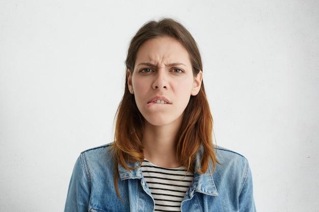 Foto de uma jovem caucasiana estressada e frustrada, vestida com roupas elegantes, mordendo o lábio inferior e franzindo a testa, sentindo-se nervosa e ansiosa