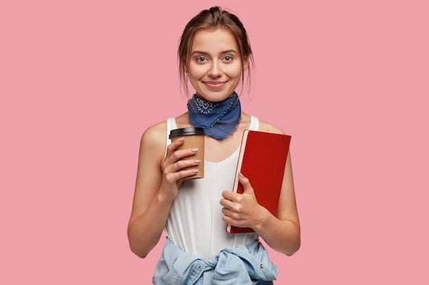 Foto de uma jovem colegial de aparência agradável, vestida com um traje moderno