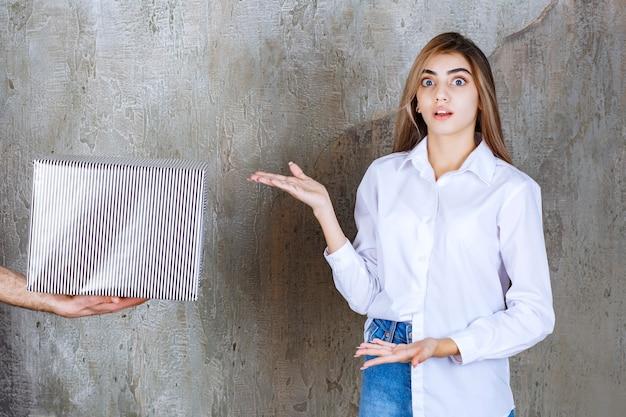 Foto de uma jovem com cabelo comprido em pé perto da caixa de presente
