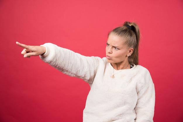 Foto de uma jovem com roupas casuais posando e apontando o dedo indicador para cima
