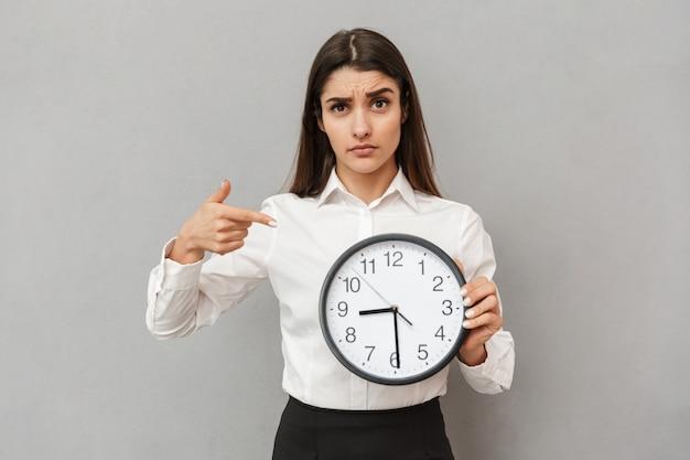 Foto de uma jovem confusa ou chateada em uma camisa branca e saia preta apontando o dedo em um grande relógio redondo segurando na mão, isolada sobre uma parede cinza