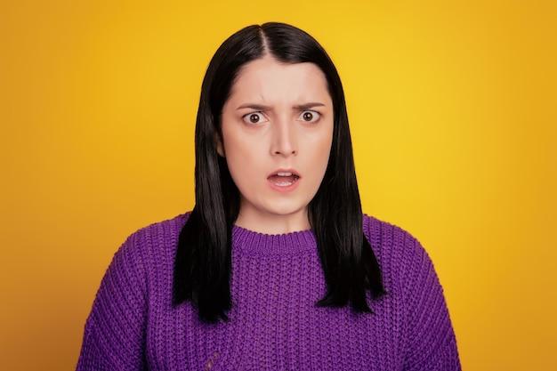 Foto de uma jovem confusa sem noção espantada e chocada com notícias falsas isoladas sobre fundo de cor amarela