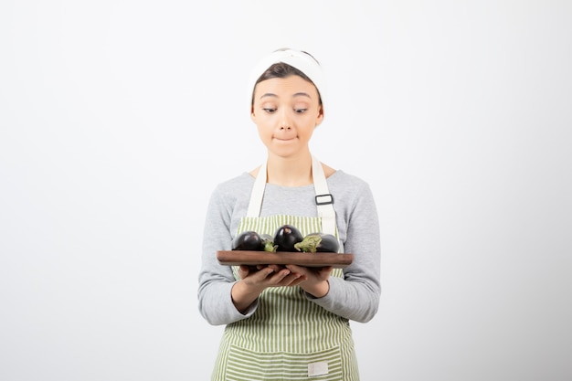 Foto de uma jovem cozinheira olhando para um prato de berinjela em branco