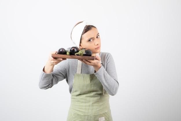Foto de uma jovem cozinheira segurando um prato de berinjelas e olhando para a câmera