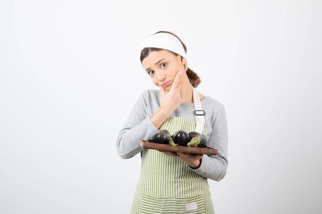 Foto de uma jovem cozinheira segurando um prato de berinjelas e pensando