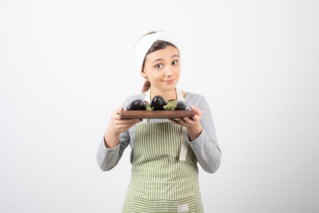 Foto de uma jovem cozinheira segurando um prato de berinjelas em branco