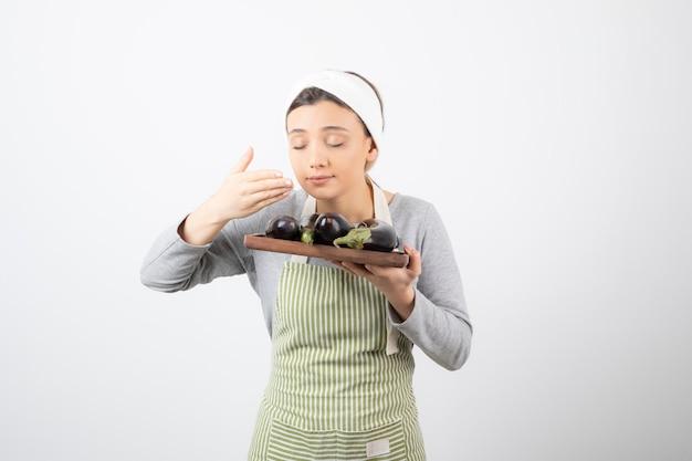 Foto de uma jovem cozinheira sentindo o cheiro de berinjela no branco