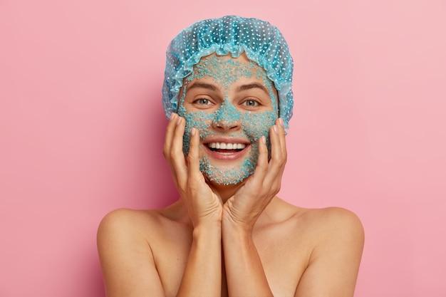 Foto de uma jovem de aparência agradável se preocupa com a pele, aplica grânulos de sal marinho no rosto, parece revigorada e feliz, fica de topless contra uma parede rosa, tem prazer em rejuvenescer