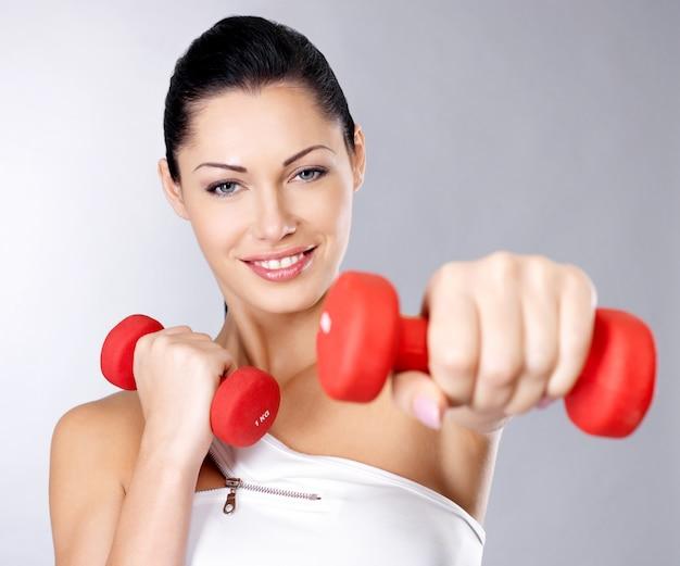 Foto de uma jovem de treinamento saudável com halteres. conceito de estilo de vida saudável.