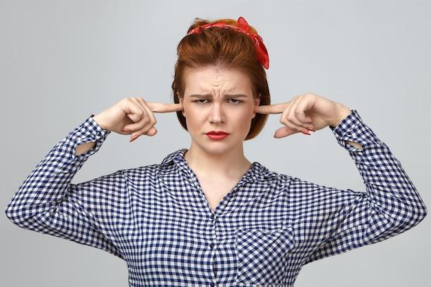 Foto de uma jovem dona de casa frustrada tendo uma aparência dolorida de cansaço, franzindo a testa e tampando as orelhas com os dedos, ficando estressada com crianças barulhentas