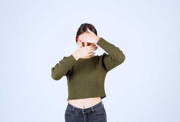 Foto de uma jovem e adorável modelo cobrindo o rosto com as mãos
