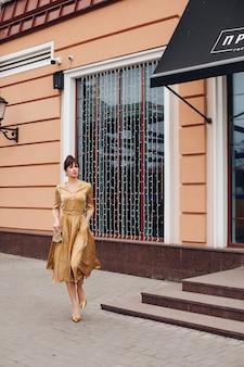 Foto de uma jovem e adorável mulher branca com cabelo escuro, vestida de ouro e sapatos dourados mostra diferentes barracas perto do belo edifício