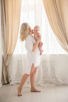 Foto de uma jovem e linda mãe com um lindo menino, mamãe sorridente levanta seu adorável filho, uma linda mulher vomitando uma criança alegre em um fundo cinza, família feliz e saudável, conceito de amor