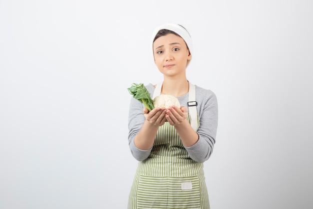 Foto de uma jovem e simpática modelo com avental segurando uma couve-flor