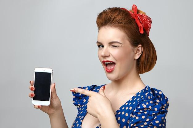 Foto de uma jovem elegante e emocional, vestida como uma garota, piscando alegremente para a câmera e apontando o dedo indicador