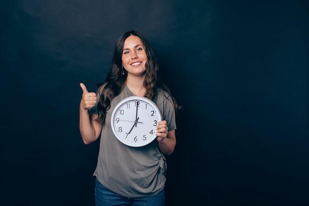 Foto de uma jovem em pé sobre um fundo preto mostrando o polegar para cima e segurando o relógio às sete horas