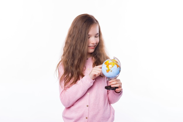 Foto de uma jovem em pé sobre uma parede branca e apontando no pequeno globo para outro destino