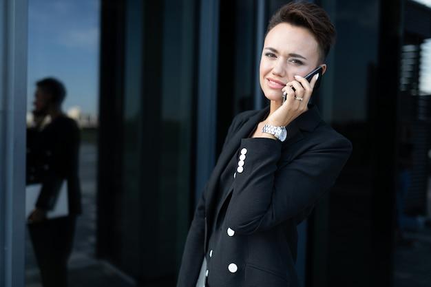 Foto de uma jovem empresária ambiciosa no fundo de um prédio de escritórios moderno
