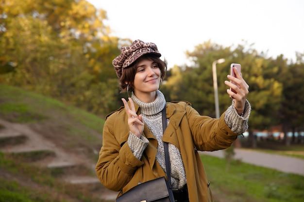 Foto de uma jovem encantadora de cabelos castanhos com penteado bob sorrindo agradavelmente enquanto faz uma selfie com seu telefone celular e levanta a mão com um gesto de vitória, em pé sobre o parque desfocado