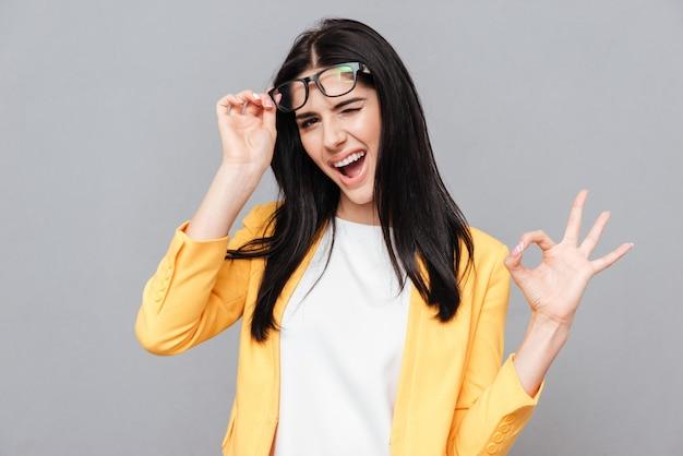Foto de uma jovem encantadora usando óculos e vestida com uma jaqueta amarela faz o gesto de ok sobre a superfície cinza. olhe para a frente.