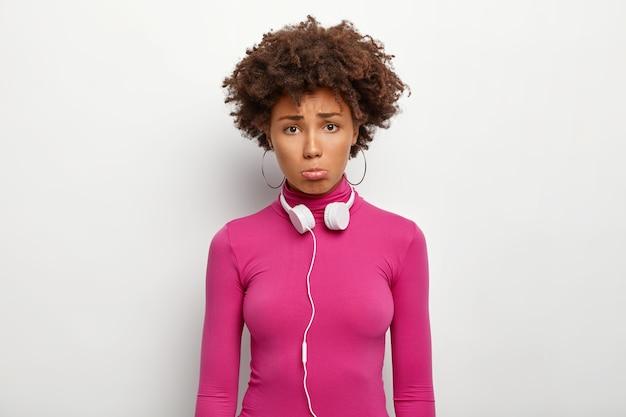 Foto de uma jovem encaracolada de cabelos escuros com olhar mal-humorado e expressão triste