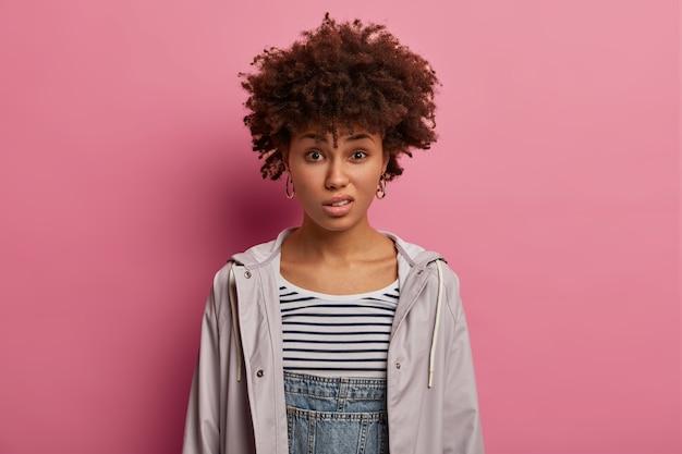 Foto de uma jovem encaracolada descontente com um sorriso afetado, tem uma reação negativa, ouve besteiras, parece insatisfeita, vestida casualmente, posa contra uma parede rosada. expressões humanas negativas