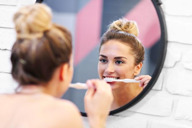 Foto de uma jovem escovando os dentes no banheiro