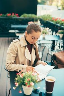 Foto de uma jovem escrevendo no planejador enquanto está sentada no café e bebe uma xícara de café