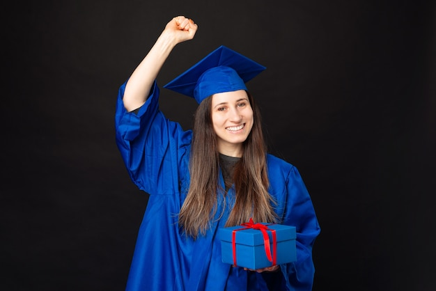 Foto de uma jovem estudante com um manto azul comemorando o sucesso e segurando uma caixa de presente