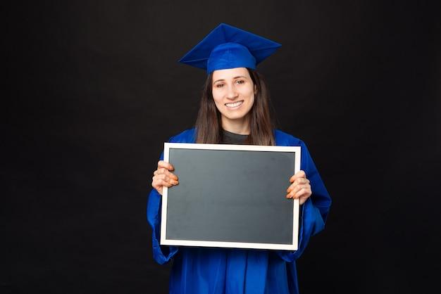 Foto de uma jovem estudante sorridente com túnica azul segurando um quadro de giz preto vazio
