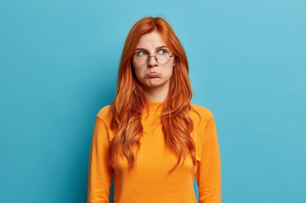 Foto de uma jovem européia ruiva ofendida com um olhar desapontado mal-humorado franzindo os lábios e desviando o olhar de descontentamento ao ouvir palavras desagradáveis usa óculos redondos e jumper casual.