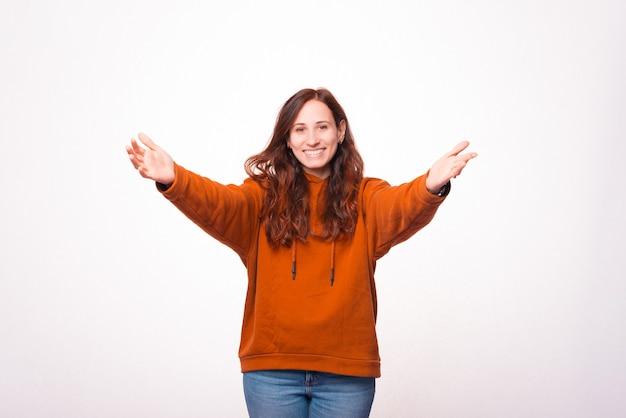 Foto de uma jovem fazendo um gesto de boas-vindas e sorrindo sobre uma parede branca