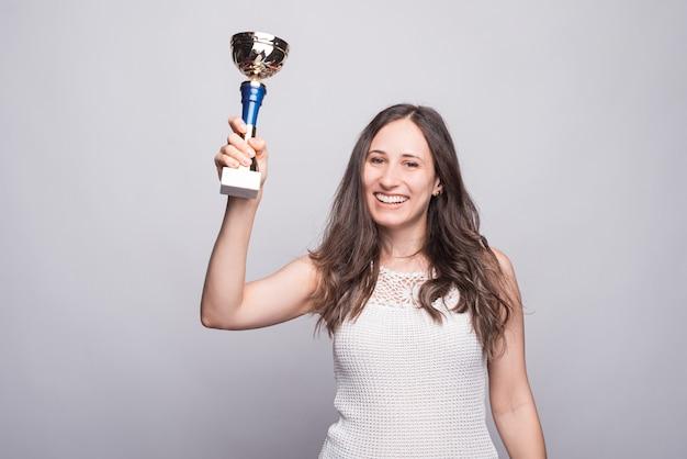 Foto de uma jovem feliz comemorando e segurando a copa dos campeões e olhando confiante para a câmera