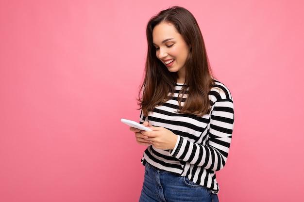 Foto de uma jovem feliz e sorridente mulher morena usando um telefone celular e se comunicando por sms