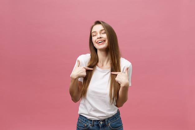 Foto de uma jovem feliz em pé e apontando o dedo