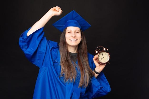 Foto de uma jovem feliz se formando e segurando um despertador
