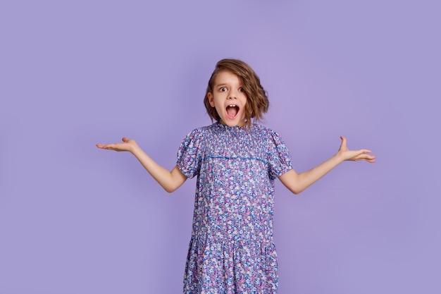 Foto de uma jovem feliz surpresa espalhando as mãos nas laterais isoladas em roxo