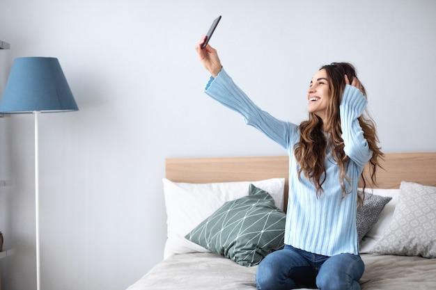 Foto de uma jovem feliz tomando selfie com seu celular enquanto está sentado na sala de estar. estilo de vida.