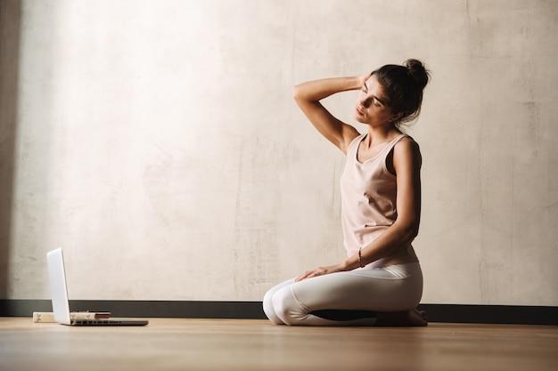 Foto de uma jovem focada em roupas esportivas fazendo exercícios com os olhos fechados e usando o laptop enquanto está sentada no chão em casa