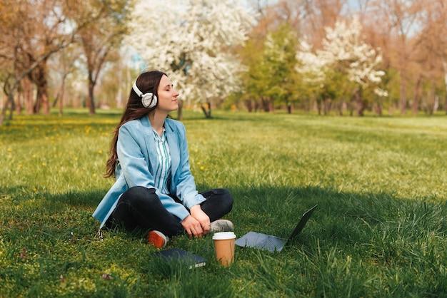 Foto de uma jovem freelance sentada na grama da cidade, no parque, ouvindo música em frente ao laptop e a xícara de café